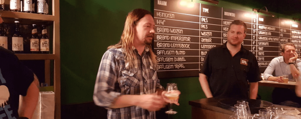 Jeremy Marshall holding glass of beer in a bar