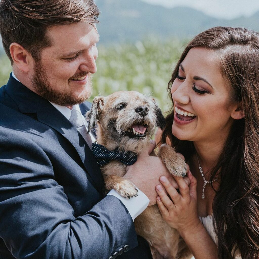 Man, dog and woman smiling